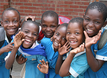 Children from Zimbabwe waving and smiling